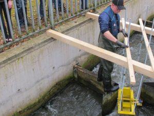 Wasserbauer Marcel Schenkel vom Lippeverband befestigt das Wasserrad im Fischpass