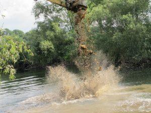 Was der Bagger am Ufer abgräbt, landet zum Teil direkt in der Lippe, um die Flusssohle anzuheben. Denn an den meisten Stellen ist die Lippe tiefer als sie sein soll.