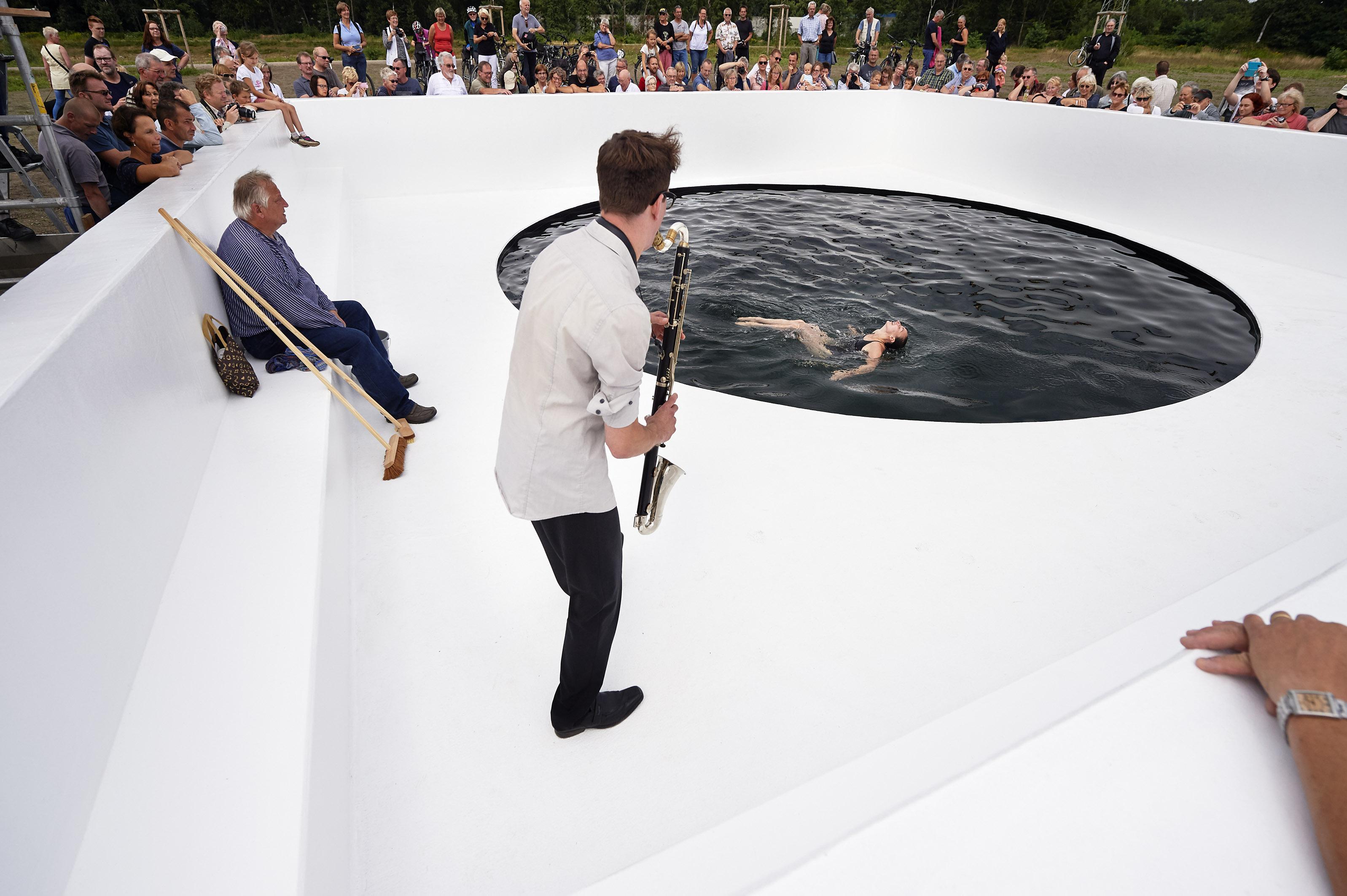 Musiker, Schwimmerin und Reiniger sind Teil des Performance-Konzeptes