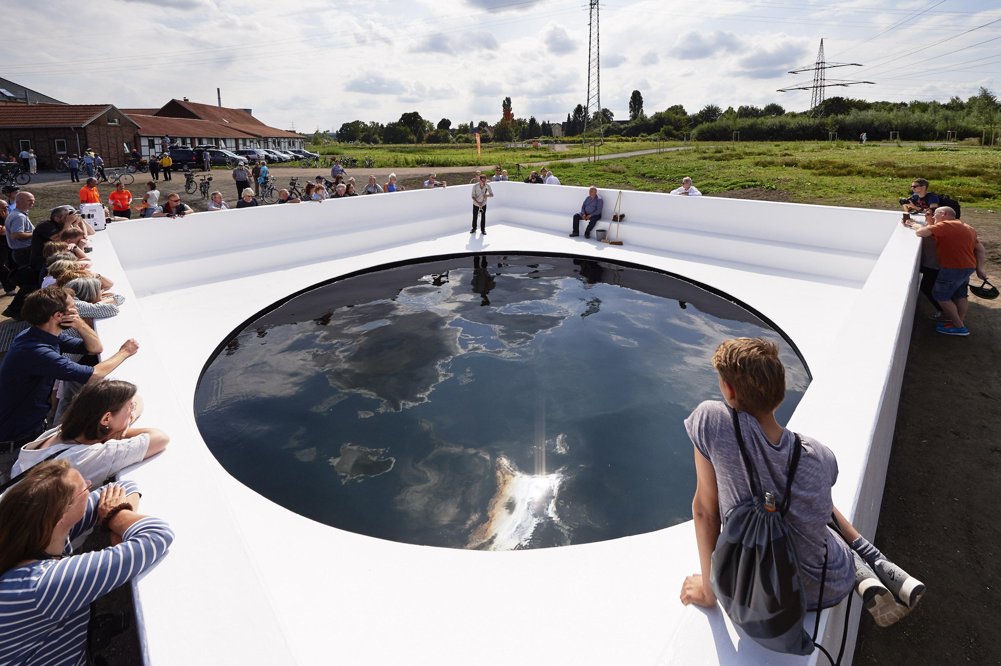 Wolken spiegeln sich in der schwarzen Oberfläche des Pool, der als Löschteich für den Emschertalhof genutzt werden wird