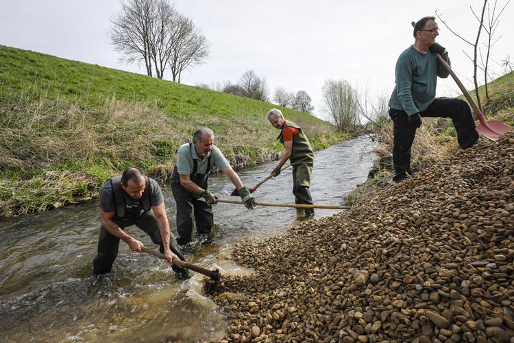 Ehrenamtliche Helfer aus Fischerei und dem örtlichen Angelverein verteilen das Material vom Wasser aus.