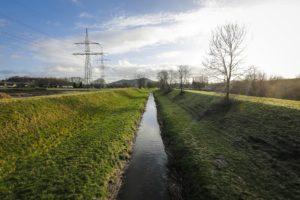 """Parallel zur Straße """"Im Gewerbepark"""" in Bottrop fließt die Boye aktuell noch schnurgerade innerhalb ihrer begradigten Trasse. Foto: Rupert Oberhäuser/EGLV"""