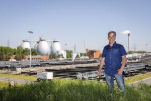 """Ulrich Florie auf """"seiner"""" Kläranlage Bottrop. Hinter ihm die markanten Faulbehälter."""
