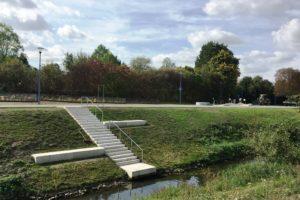 Auch hier führt ein Treppe ans Ufer, auf den Sitzflächen kann man es aushalten. Im Hintergrund sieht man die wellenförmige Spielanlage. Foto: EGLV