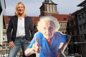 """Andrea Holte im Essener Gebäudeinnenhof neben dem Kampagnen-Testimonial """"Oma Klara"""" (hier in Form eines Aufstellers). Foto: Celina Winter/EGLV"""